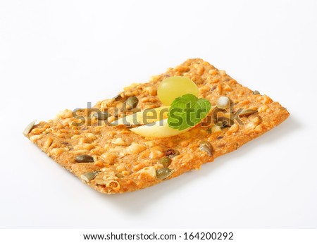 slice of seeds crispy bread decorated with apple and grape - stock photo