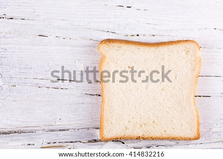 slice of toast on white wooden background, closeup with copy-space - stock photo