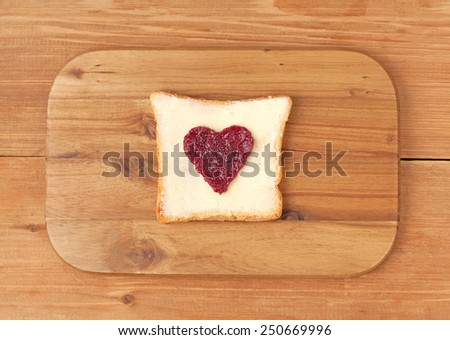 Slice of wholewheat toast with red berry jam and butter in the shape of heart on wooden background