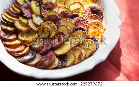Sliced and roasted potatoes with rosemary in a shallow baking dish on a red silk tablecloth.  - stock photo