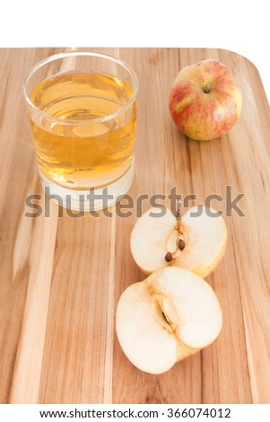 Sliced and whole apple on cutting board with glass of apple juice