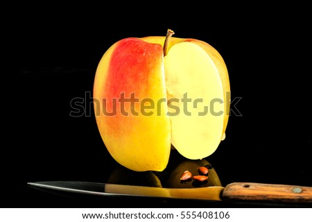 Sliced Apple, knife and fallen seeds lie on a black glass table with reflection
