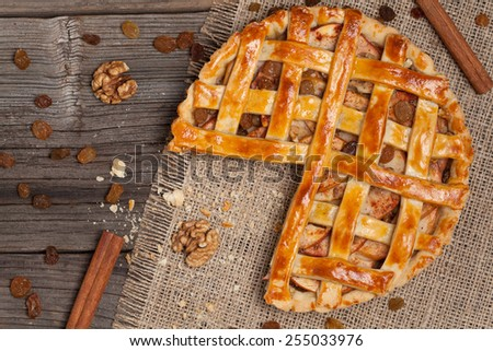 Sliced apple pie with crumbs on wooden table texture - stock photo