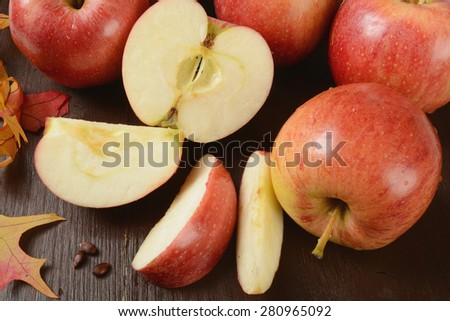 Sliced apples on a rustic wooden table with autumn leaves - stock photo