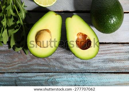Sliced avocado, arugula on wooden background - stock photo