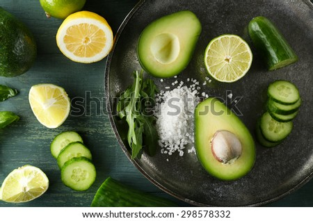 Sliced avocado, cucumber/ pepper and lemon lime on wooden background - stock photo