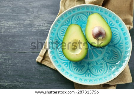 Sliced avocado on plate, on wooden background - stock photo
