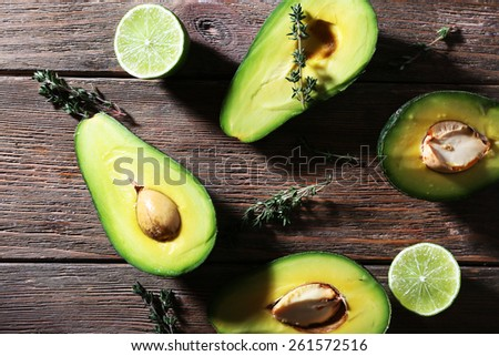 Sliced avocado with herb and lime on wooden background - stock photo