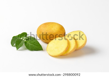 sliced baby potatoes with leaves on white background