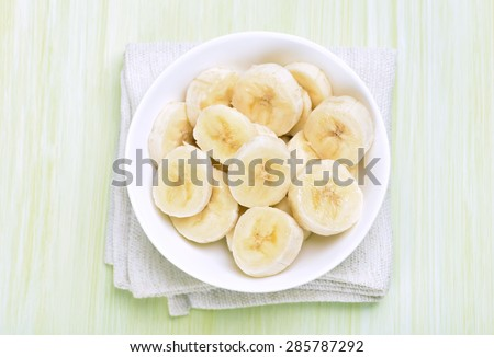 Sliced banana in the bowl, top view - stock photo