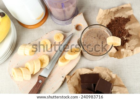 Sliced banana on cutting board and chopped chocolate, on wooden background - stock photo