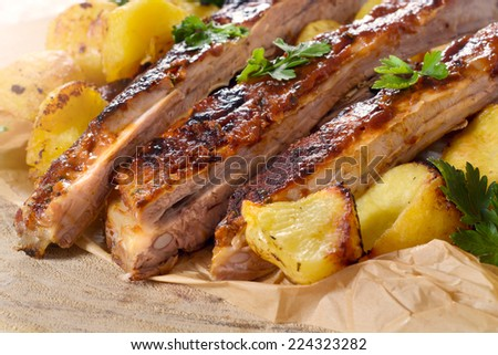 Sliced beef ribs in bbq sauce and baked potatoes,selective focus - stock photo