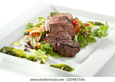 Sliced Beef Steak on Fresh Salad Leaf with Pesto Sauce - stock photo