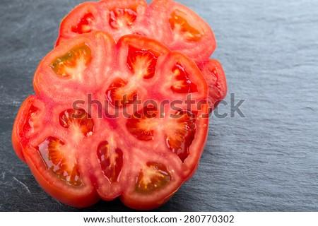 Sliced Beef Tomato on black background - stock photo