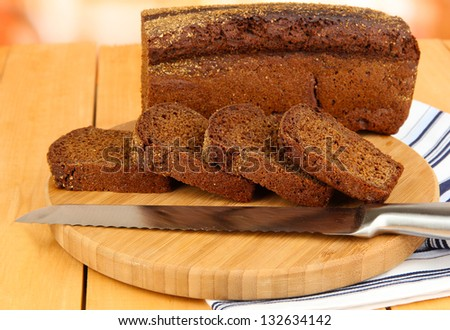 Sliced black bread and knife on chopping board on wooden table close up - stock photo