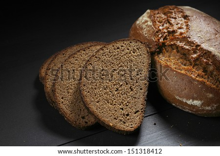 Sliced black bread on wooden table close-up - stock photo
