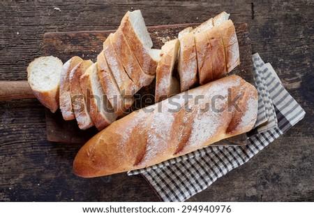 sliced bread for bruschettas on wooden cutting board - stock photo