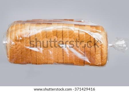 Sliced bread in plastic bag. - stock photo