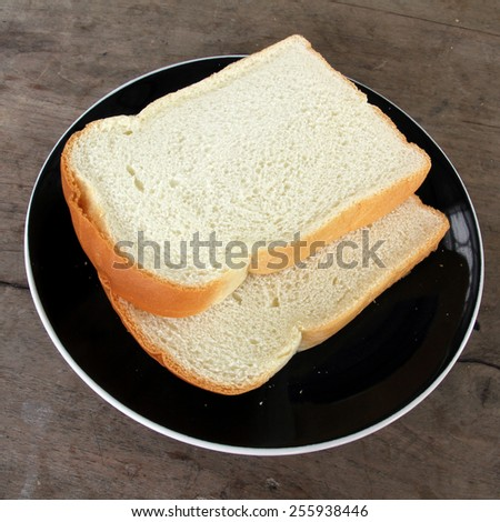 Sliced bread on black plate on old wooden background.  - stock photo