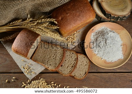 Sliced bread on textile. Bread on wooden table. Flour in wooden plate. wheat on a wooden table.With wooden and textile background.  Top view