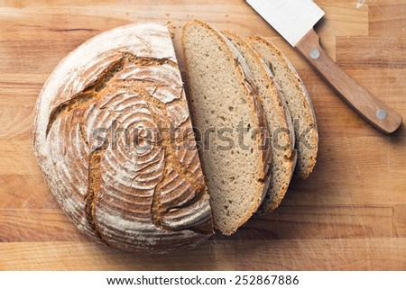 sliced bread on wooden table - stock photo