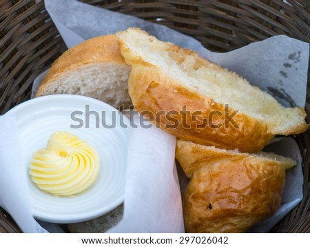 sliced bread with butter and knife in the wood basket - stock photo