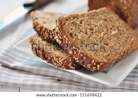 Sliced bread with sunflower seeds and sesame on a plate - stock photo