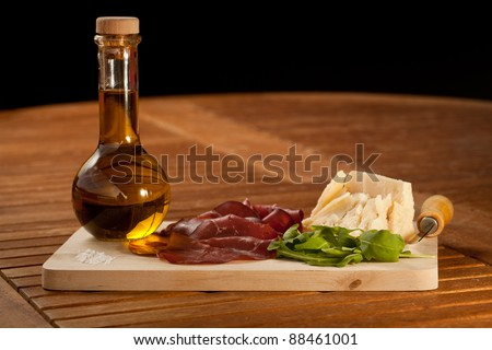 Sliced bresaola ham with salad and parmesan cheese with an oil bottle, over a wooden chunk-board