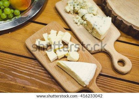 sliced brie cheese slices on a wooden stand.