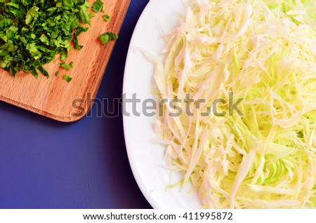 Sliced cabbage in a dish on the table. Chopped parsley and chopped cabbage - stock photo