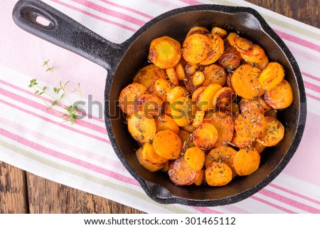 Sliced carrots roasted with herbs in a cast iron skillet. Top view. - stock photo
