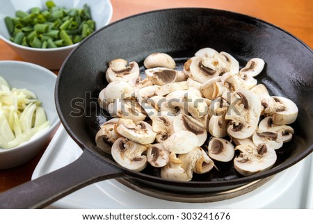 Sliced champignon mushrooms on cast iron skillet ready to cook mushroom sauce , chopped onions and chives on left - stock photo