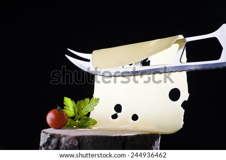 Sliced cheese and cheese knife on the stump - stock photo