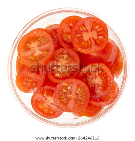 Sliced cherry tomatoes in glass bowl isolated on white, view from directly above. - stock photo