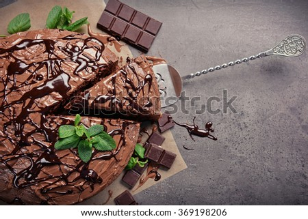 Sliced chocolate pie with mint and ingredients on table - stock photo