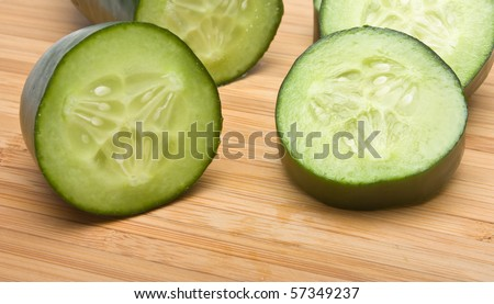 Sliced Cucumber from low perspective on wooden bamboo chopping board.