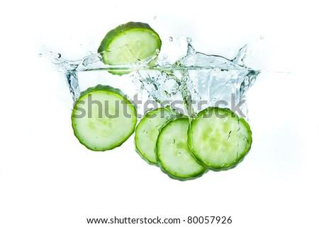 sliced cucumber splashing water isolated on white background - stock photo