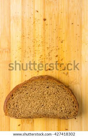 Sliced dark bread with crumbs on wood board - stock photo