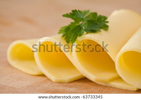 Sliced delicious edam cheese on wooden board with selective depth of field - stock photo