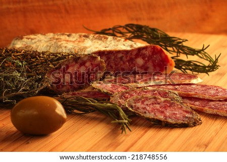 Sliced dried french sausages with rosemary and olive on wooden table