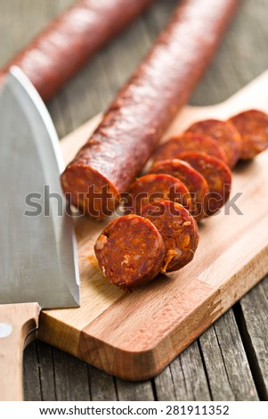 sliced dried sausages on old wooden table - stock photo
