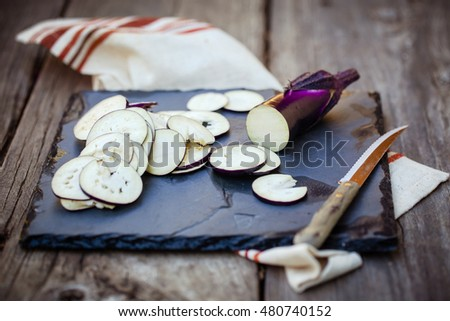 Sliced eggplants on a black board with wooden background. Also available in vertical format.
