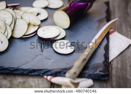 Sliced eggplants on a black board with wooden background. Close up. Also available in vertical format.