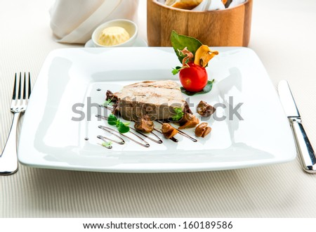 Sliced foie gras with sauce and chanterelle mushrooms   - stock photo