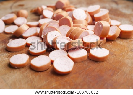sliced frankfurter sausages on wood chopping board - stock photo
