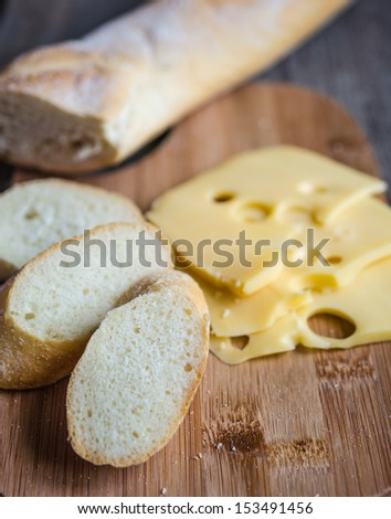 Sliced french baguette and cheese - stock photo