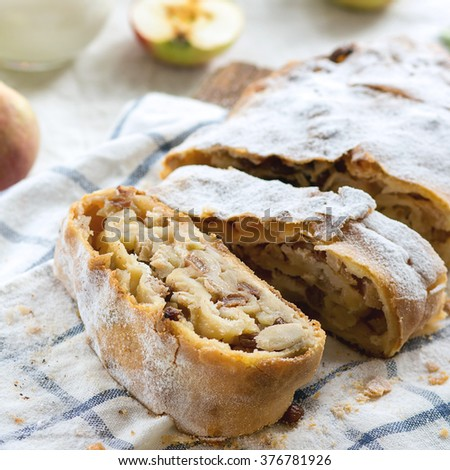 Sliced fresh baked homemade apple strudel over towel on kitchen table with jug of milk and apples. Rustic style. Natural day light. Square image with selective focus - stock photo
