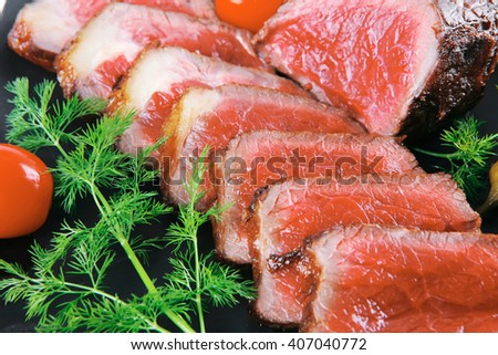 sliced fresh meat on dark plate with tomato and fennel - stock photo