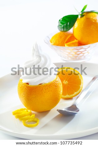Sliced fresh orange topped with twirling creamy softserve ice-cream served on a white plate with copyspace - stock photo
