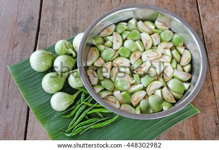 Sliced fresh organic eggplant in water and green chilli on banana leaf against wood table - stock photo